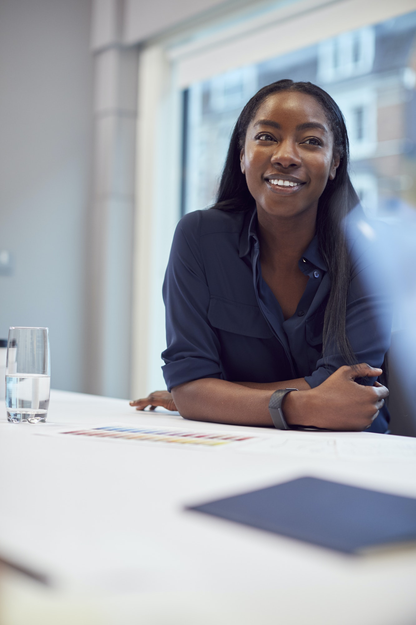 Smiling African American Businesswoman Sitting At Table In Office Meeting Room