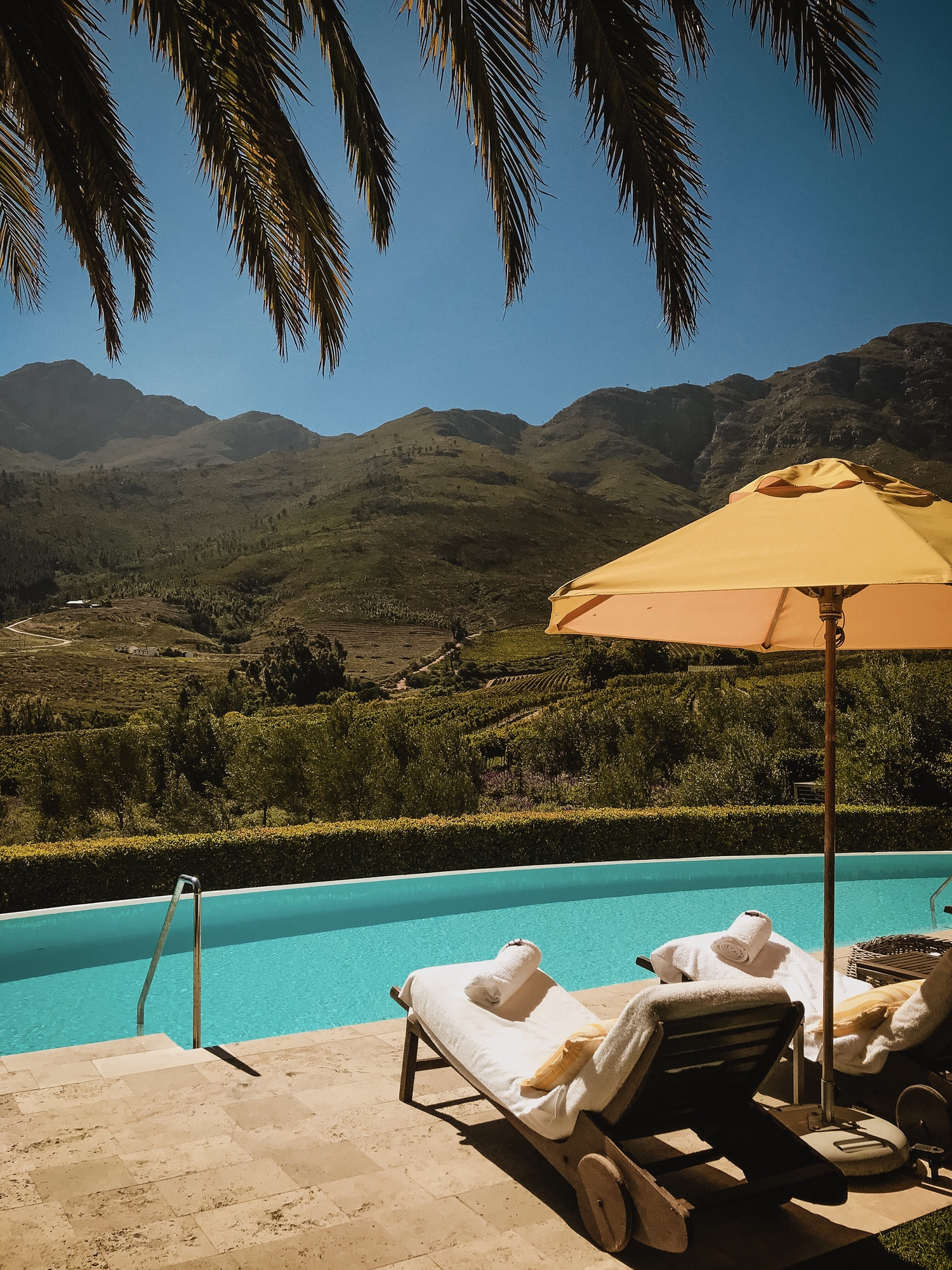 Swimming pool day beds with a gorgeous view and a yellow umbrella for some shade